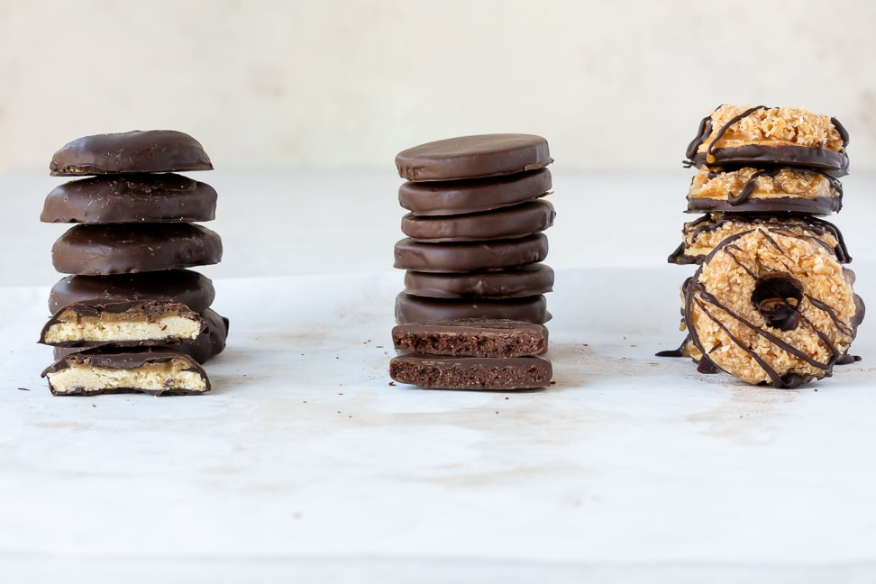 stacks of thin mint, tagalong and samoa cookies on a white surface with one cookie placed in front of stack for display