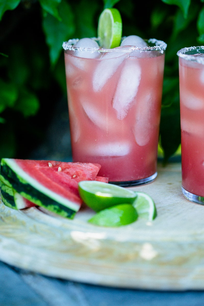 Watermelon Margaritas (Paleo & Refined Sugar-Free) served in glass tumblers full of ice and garnished with a lime next pieces of fresh watermelon and slices of lime