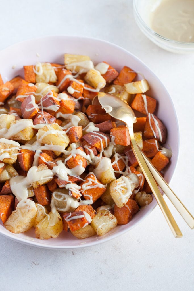 white bowl with gold colored spoon full of Roasted Pineapple and Sweet Potatoes with Cinnamon Cashew drizzle